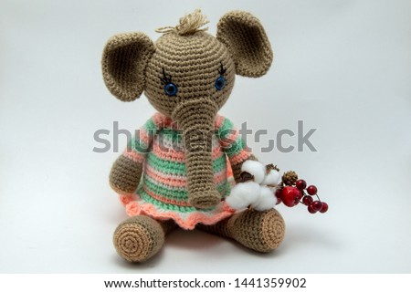 Amigurumi doll is a little elephant sitting on a white background.