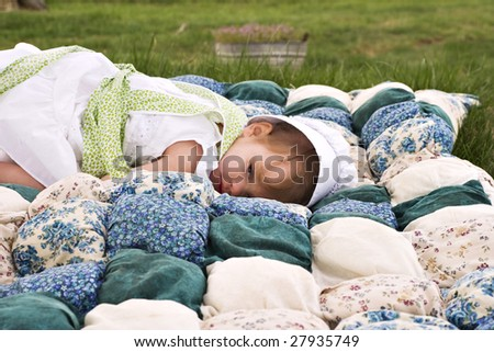 Amish child lying outdoors on a handmade biscuit quilt.