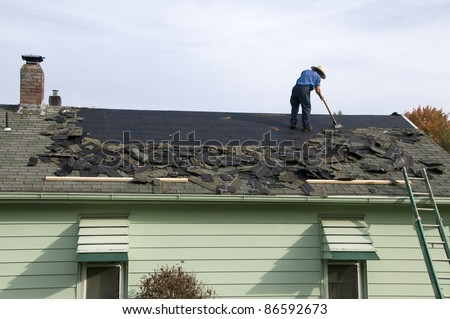 Amish workman removing old shingles to prepare a roof for a new installation