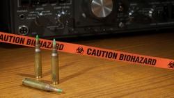 Ammunition, ham radio in the background and orange biohazard tape