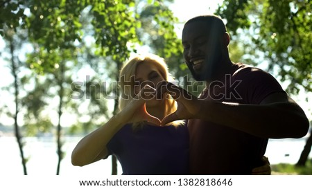 Amorous mixed race couple showing heart shape with hands, interracial marriage