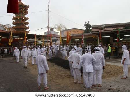 AMPANG, MALAYSIA – OCT 05: Devotees pound the charcoal in preparation for the fire-walk pit at the Lam Thian Kiong Temple during the annual 'Nine Emperor Gods' Festival on October 05, 2011 in Ampang, Malaysia.