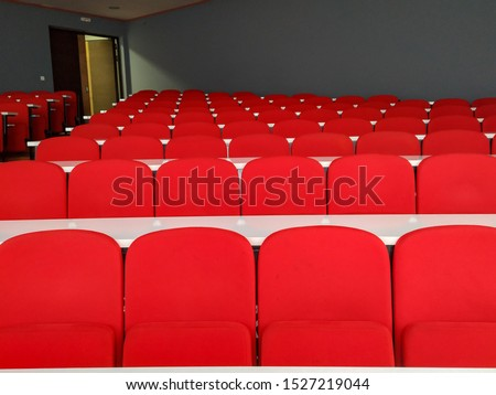 Amphitheater big lecture room with red chairs and white tables for students lined in rows for university or conference lectures #1527219044