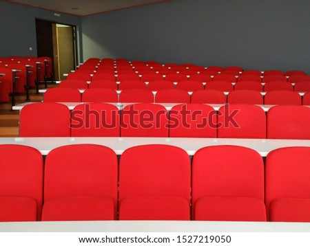 Amphitheater big lecture room with red chairs and white tables for students lined in rows for university or conference lectures with doors in background #1527219050