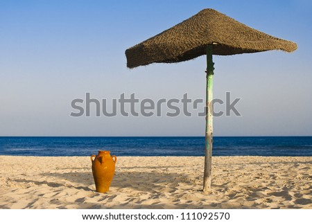 Amphora and an umbrella on the beach with sea in the background