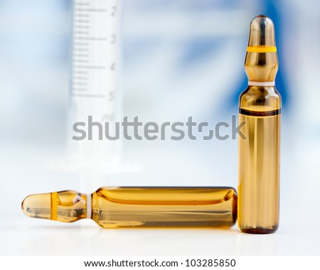 Ampoules containing yellow drug with blurred blue background