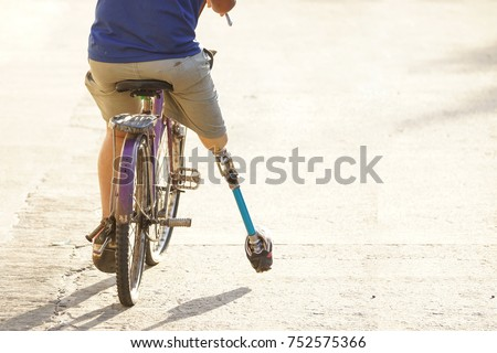 Amputee on a bicycle with copy space to add text