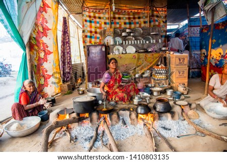 AMRAVATI, MAHARASHTRA, INDIA, 22 JANUARY 2018 : Unidentified woman making and cooking fresh food in village at vintage kitchen using firewood in earthen chulhas, daily lifestyle in rural area in India #1410803135