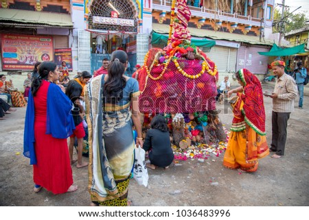AMRAVATI, MAHARASHTRA, INDIA, MARCH - 1, 2018: unidentified people celebrating Holika Dahan by worshiping of wood logs or coconut. also known as the festival of colours Holi or the festival of sharing #1036483996