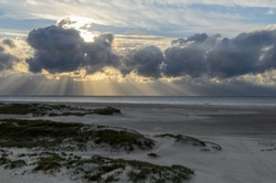 Amrum island, Germany: sun rays emerging through the dark storm clouds at the beach of Amrum. Sunset is obscured by a thick cloud front announcing bad weather