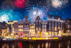 Amstel river, canals and boats against night cityscape of Amsterdam with fireworks, Holland Netherlands