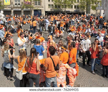AMSTERDAM - APR 30: City natives and tourists celebrate Queen's Day, Dutch annual national holiday, in the streets of the city, April 30, 2011, Amsterdam, The Netherlands
