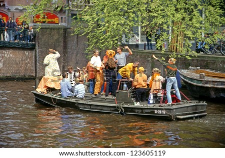 AMSTERDAM - APRIL 30: City natives and tourists celebrate Queen's Day, Dutch annual national holiday, in the streets of the city, on April 30, 2001 in Amsterdam, The Netherlands