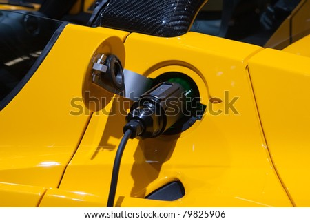 AMSTERDAM - APRIL 22 - Electric cable plug into electric sports car socket on display at the AutoRAI motorshow. April 22, 2011 in Amsterdam, The Netherlands. - stock photo
