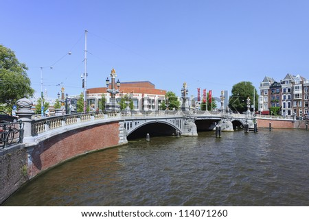 AMSTERDAM-AUG. 19: Ancient bridge with opera house on Aug. 19, 2012 in Amsterdam. It is known as Venice of the North, its beautiful canal belt was added to world heritage list in July 2010.