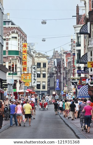 AMSTERDAM-AUG. 19: Tourists in The Damstraat. The city has 15,749,000 annual visitors,  37,763 hotel beds, 6,800 16th-, 17th- and 18th-century buildings and 51 museums. Amsterdam, Aug. 19, 2012.