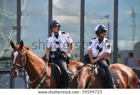AMSTERDAM- AUGUST 19 : Female police officers on horseback watch the crowd at Sail 2010 in Amsterdam, Holland on august 19, 2010