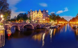 Amsterdam canal, bridge and typical houses, boats and bicycles during evening twilight blue hour, Holland, Netherlands. Used toning.