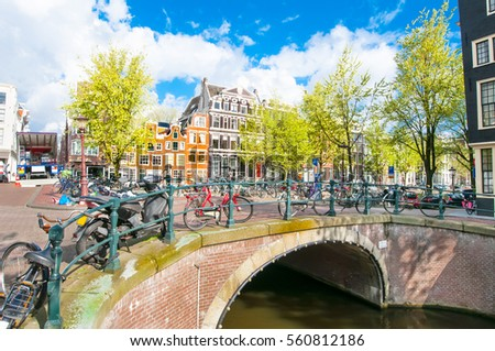 Amsterdam cityscape with bikes on the bridge during the middle spring, Netherlands. #560812186