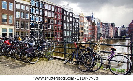 AMSTERDAM, HOLLAND - AUGUST 01: Traditional houses of Amsterdam, Holland. August 01, 2012 Amsterdam, Holland. A lot of bicycles parked in front of the traditional houses. Typical Amsterdam view.