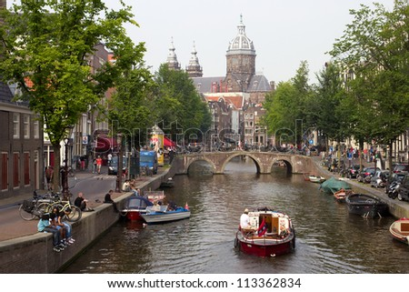 AMSTERDAM, HOLLAND-JULY 27: Canal and bridge on July 27, 2012 in Amsterdam. It is known as Venice of the North, its canal belt was finally added to the world heritage list in July 2010.