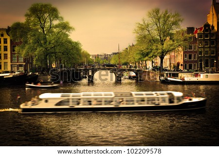 Amsterdam, Holland, Netherlands. Romantic bridge over canal, cabin cruiser. Old town - stock photo