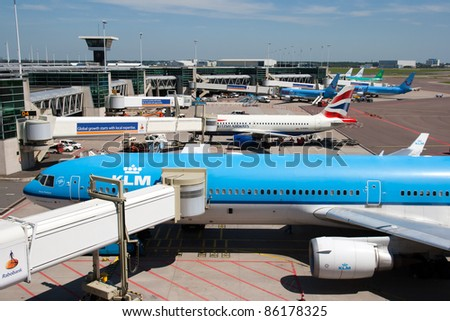 AMSTERDAM - JUNE 27: Planes at Schiphol Airport June 27, 2011 in Amsterdam, Netherlands. The airport handles over 45 million passengers per year with almost 100 airlines flying from here.