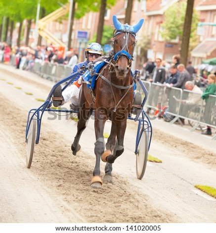 AMSTERDAM - JUNE 1: Unidentified driver and his horse participate in the annual short distance horse race held in the van der Pek street of the city, June 1, 2013,  Amsterdam, The Netherlands