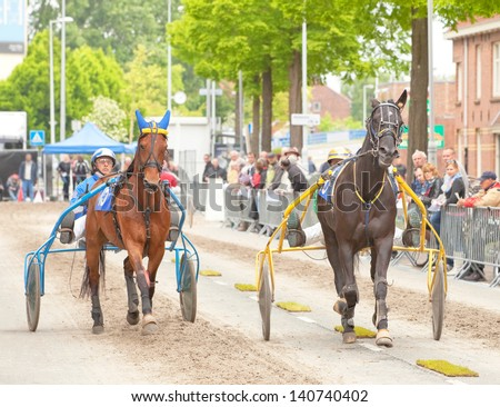 AMSTERDAM - JUNE 1: Unidentified drivers and their horses participate in the annual short distance horse race held in the van der Pek street of the city, June 1, 2013,  Amsterdam, The Netherlands