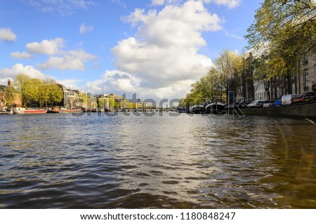 Amsterdam/Netherlands/04.24.2016. Amsterdam's canal with old barges moored along the banks converted into houseboats and a bridge in the background. #1180848247