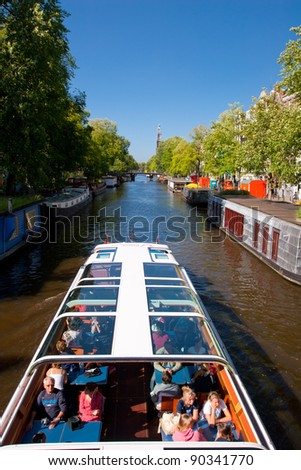 AMSTERDAM, NETHERLANDS - AUG 11: Tourist boat cruises on canal in Amsterdam on August 11, 2008.  Almost 20 percent of all canal cruise boats are now electrically powered