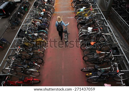 AMSTERDAM, NETHERLANDS - AUGUST 9, 2012: Woman pushes a bicycle on through the bicycle parking station next to the Central railway station in Amsterdam, Netherlands.