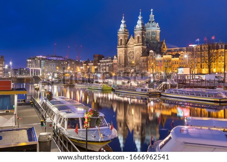 Amsterdam, Netherlands canal scene at night with Basilica of Saint Nicholas and riverboats.
