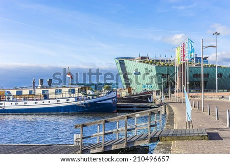 AMSTERDAM, NETHERLANDS - JUNE 17, 2014: Science Center NEMO designed by Renzo Piano (1997), it is largest children's science museum and center of tourism in the Netherlands. #210496657