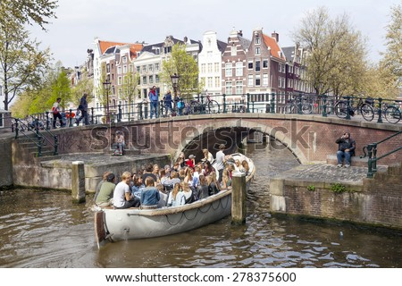 Amsterdam, Netherlands, 10 May 2015: open boat full of young people enters Prinsengracht under bridge in Amsterdam canal on sunny spring day