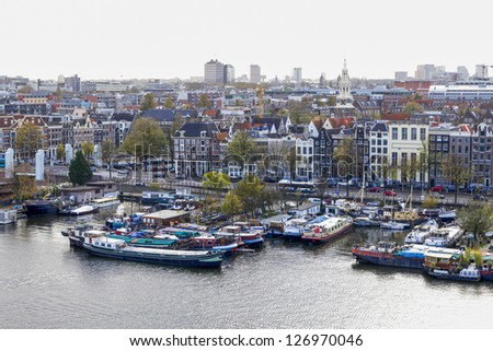 AMSTERDAM, NETHERLANDS-NOV 11: View on Amsterdam and boats on the IJ river on Nov 11, 2009. Amsterdam is included by UNESCO in the list of World Heritage
