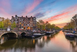 Amsterdam Netherlands, sunset city skyline of Dutch house at canal waterfront