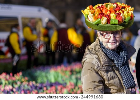 AMSTERDAM, NL - JANUARY 17: Old woman shows a tulip hat on the National Tulip Day in Amsterdam, January 17, 2015. The start of the new tulip season is celebrated with free tulip picking on Dam Square.