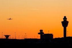 Amsterdam-Schiphol airport skyline sunset at a clear sky with airplane