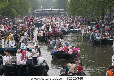 AMSTERDAM, THE NETHERLANDS - AUGUST 6: Crowd on boats in the Amsterdam canals during the famous Canal Parade of the Amsterdam Gay Pride 2011 on August 6, 2011 in Amsterdam.