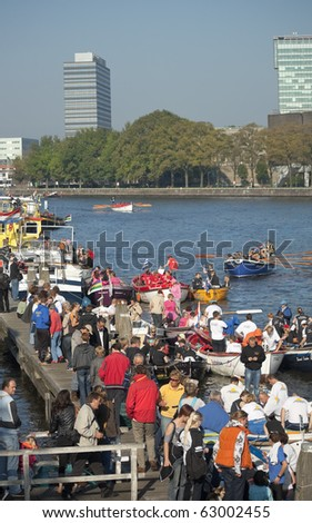 AMSTERDAM, THE NETHERLANDS - OCT 9: Participants of the annual 25 km long rowing canal race meet together after having crossed the finish line, October 9, 2010 in Amsterdam, The Netherlands - stock photo