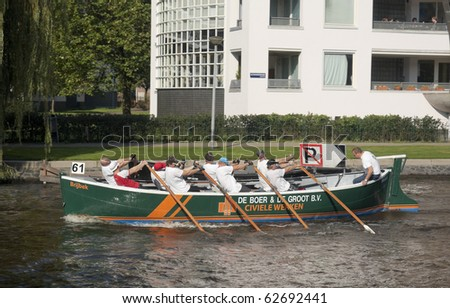 AMSTERDAM, THE NETHERLANDS - OCT 9:  Rowing team from Dutch Workum participates in the annual 25 km long canal race, October 9, 2010 in Amsterdam, The Netherlands