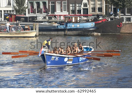 AMSTERDAM, THE NETHERLANDS - OCT 9: Rowing team from the town of Kortgene participates in the annual 25 km long city canal race, October 9, 2010 in Amsterdam, The Netherlands
