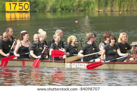AMSTERDAM, THE NETHERLANDS - SEPT 3: Unidentified Dutch team rowers participate in Dragon boats Regatta-2011 on September 3, 2011 in Amsterdam, The Netherlands