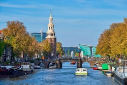 Amterdam cityscape with canal boats and medieval houses and NEMO Science museum and Montelbaanstoren Tower. Amsterdam, Netherlands
