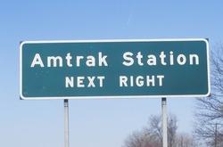 Amtrak Station sign along a highway