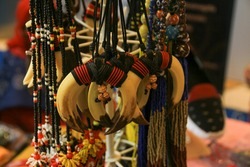 Amulets from and teeth of animals hang on laces on the stand at the fair