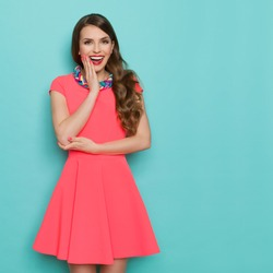 Amused beautiful young woman in pink mini dress posing with hand on chin and looking at camera. Three quarter length studio shot on turquoise background.