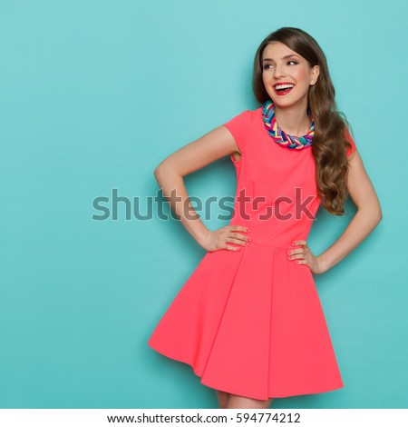 Amused beautiful young woman in pink mini dress posing with hand on hip and looking away. Three quarter length studio shot on turquoise background.