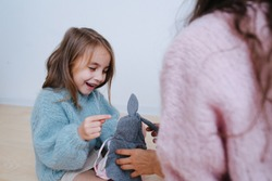 Amused little girl in a blue sweater playing with her grandma. They play with rag doll in a grey rabbit ears cloak. Sitting on a parquet at home.